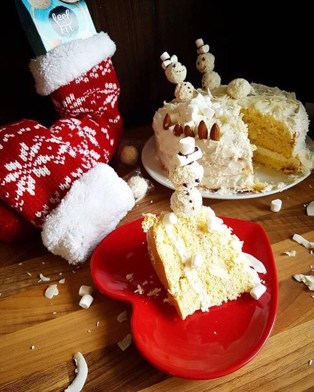 a piece of healthy cake with no added sugar, with almonds and protein coconut balls feel FIT which are snowmans on the christmas table
